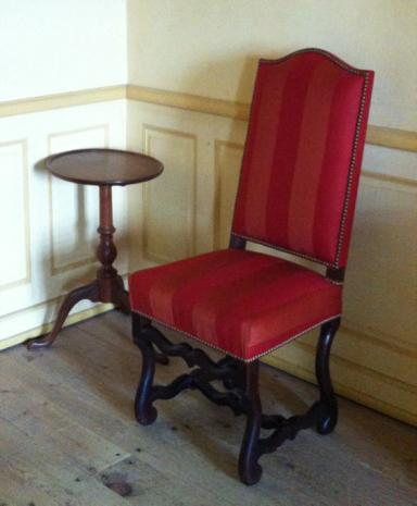 Conçu pour tenir un bougeoir, un « candlestand » de la Nouvelle-Angleterre côtoie une chaise française ou canadienne dite « os de mouton » dans la maison du commissaire ordonnateur à Louisbourg, Parcs Canada